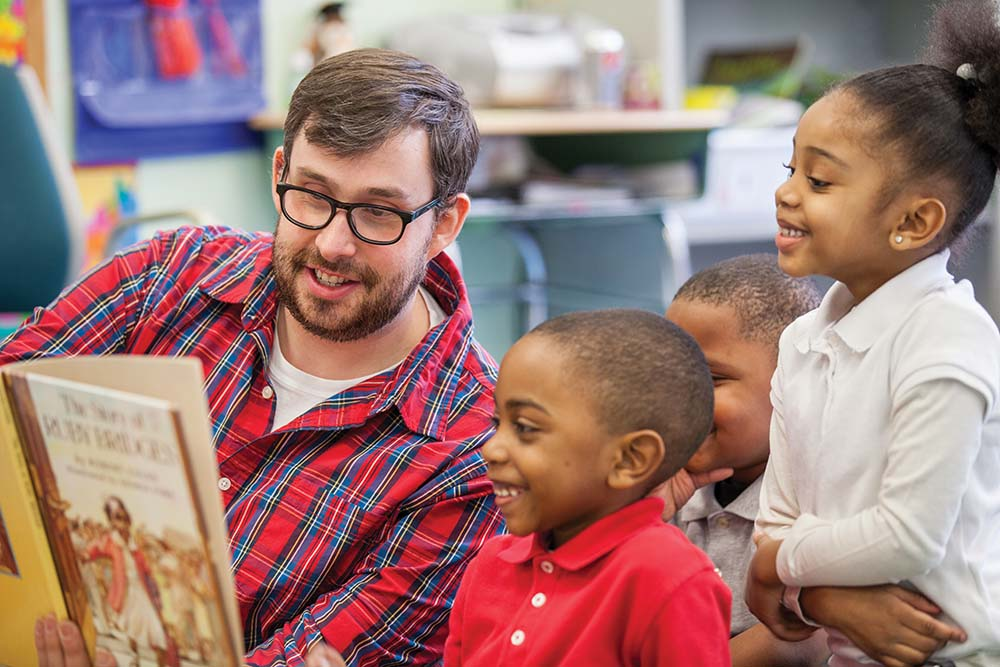 Brian Walsh, Kindergarten teacher at Chester Charter School for the Arts, reads with his students. Photo courtesy of Paul Benson