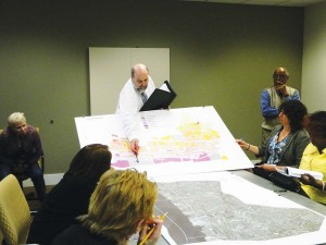 Development consultant Charles Schmel shows visitors the zone map of Chester City, explaining the difference between residential and commercially designated parcels.
