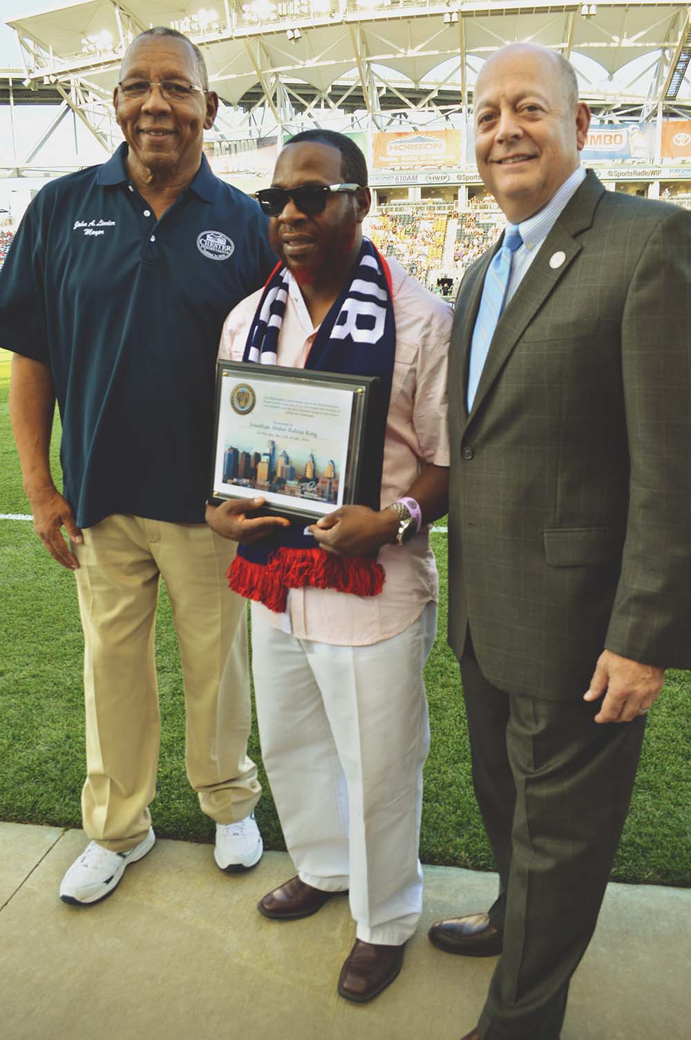 Chester Mayor John Linder (left) and Rick Jacobs, PPL Park's vice president of community affairs (right), flank and congratulate Chester community liaison and longtime activist Jonathan Abdur-Rahim King for being named a Hometown Hero.