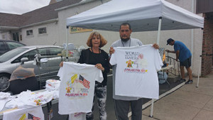 "Kelly Riddaugh and her friend Vernon ""Bo""  Barbett display the commemorative pope t-shirts they were (not) selling at the Marcus Hook train station."