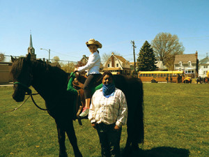 "Dujuana Ambrose-Dessau, principal of Evans Elementary School, dressed as a cowgirl with student Evangelina Elides and ""Achilles."""