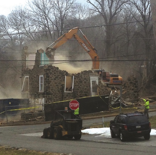 Construction workers demolish the historic Lister property on Aston Mills Road. The structure was deemed uninhabitable and a hazard to residents.