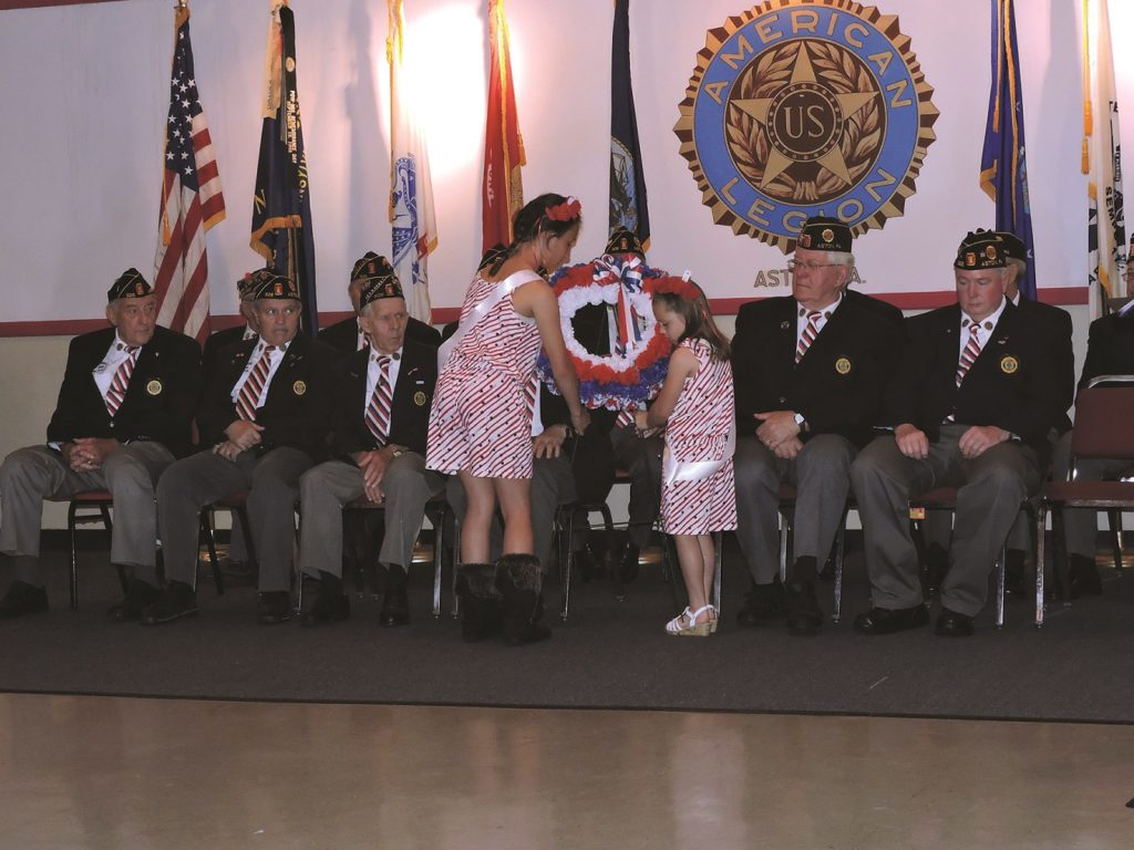 With members of American Legion Post #926 looking on poppy queens Cara DePaolantonio and Kayla Riley lay a wreath.