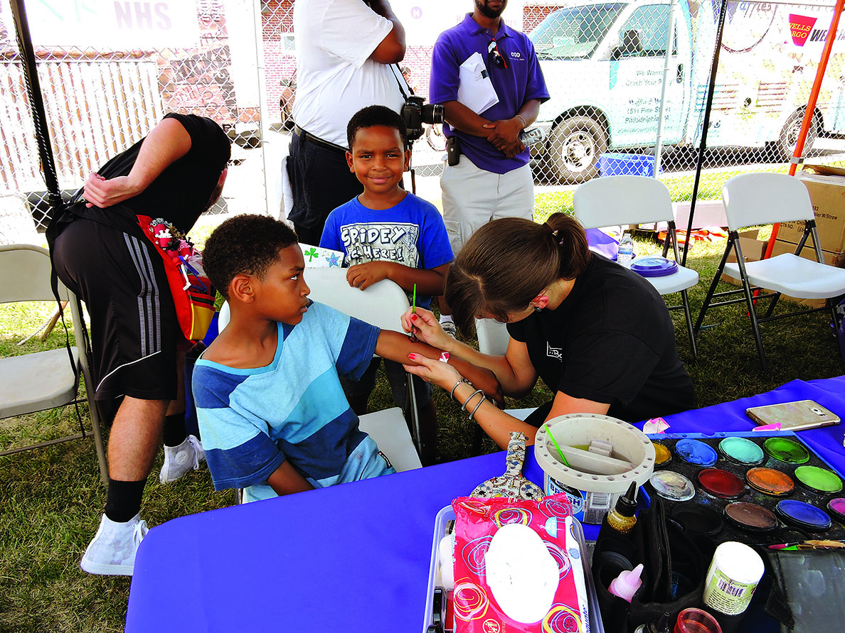 Colleen Magnuson paints a character on the arm of Jacob Gillis while his brother, Joshua, waits his turn.