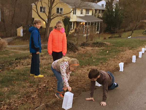 The Staley-Bischoff family was one of many that participated in the 2017 luminaria to benefit ABC Strath Haven. Siblings Wyatt (left) and Avery (right) watched as their sister, Elsie, and brother, Owen, placed bags near the curb of their house.