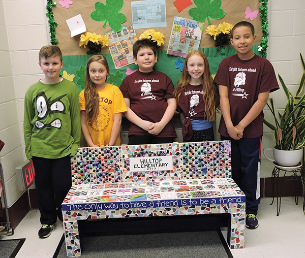 Hilltop Elementary students Ryan Bartholf, Sophia Pezzotti, Brian Parkinson, Chloe Hally and Jalyn Tidwell pose with their school's new buddy bench.