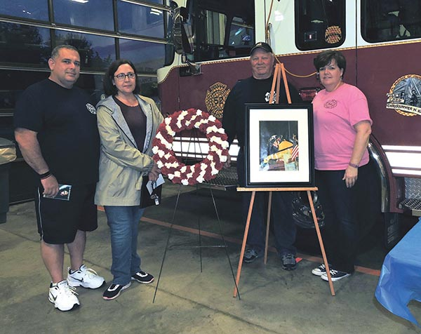 Julie Amber-Messick (second from right), mother of fallen junior firefighter Christopher Kangas, poses in front of a picture of her son with Brookhaven Fire Chief Rob Montella, Fire Company President Jon Grant and Patti Montella, who organized last week's memorial service.