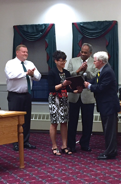 Presenting Fern Mathis (second from left) with a proclamation upon her retirement was (from left) Glenwood Elementary School Principal Eric Bucci, husband, Lamont Mathis, and Media Mayor Bob McMahon.