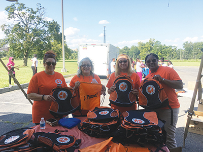 Chester Upland staff gives away bookbags.