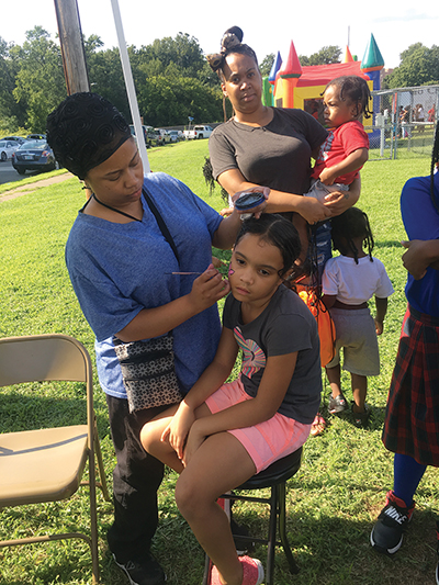 Serenity Acree, 7 gets her face painted as her mother, Lauren Carter, watches.