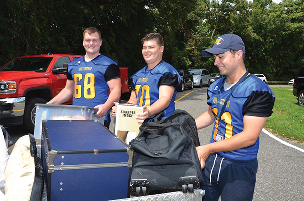 Football team members (left to right) Mark Chamberlain, Ian Waterbury and Garrett Huffman loaded items into a golf cart.