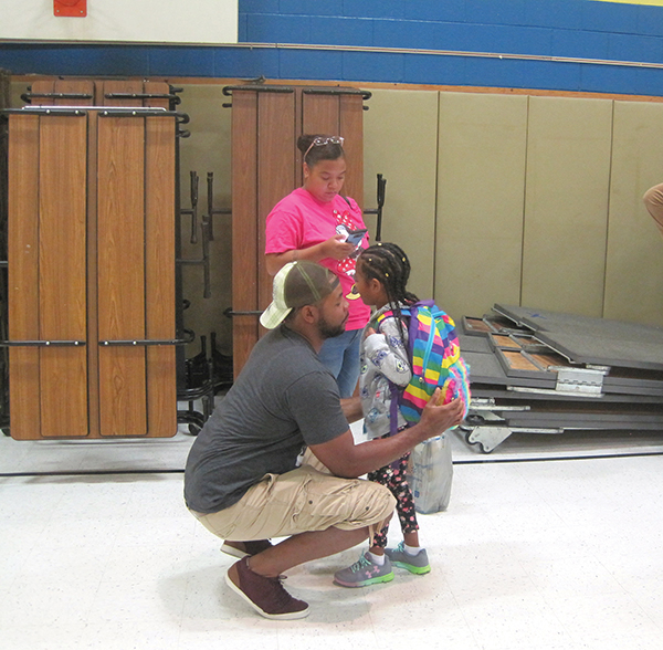 Chris Harper stoops down to whisper encouraging words to his daughter, Sarai, 7, with mom, Shannon Sampson in the background, on the first day of school at Stonehurst Hills Elementary School.