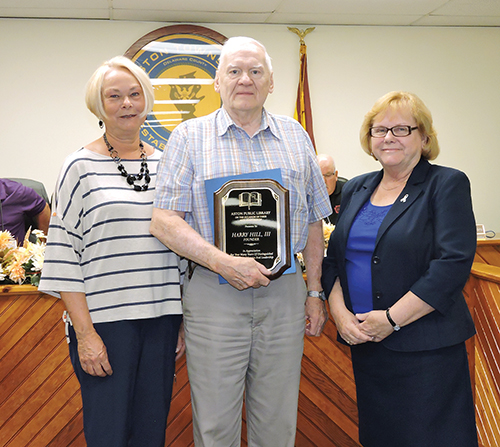 Commissioner Carol Graham and Aston Library Board of Trustees member Madelyn Bush presented Trustees President Harry Hill with a proclamation for his dedication to the library.
