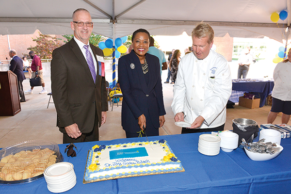 President Dr. L. Joy Gates Black cuts the ceremonial cake at the college's 50th anniversary celebration. Pictured with her are (from left) Board of Trustees Chairman Michael Ranck and Chef Peter Gilmore,directorof the college's Culinary Arts program.