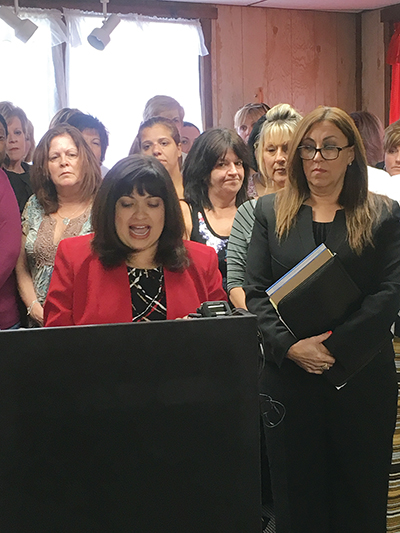 Former Chester City Controller Dalinda Carrero-Papi (at podium)and Kathy Piperino (glasses in black suit), an attorney and women's advocate, blast Democratic County Council candidates for creating a computer app that encourages verbal abuse against women.