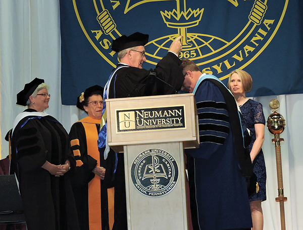 With Dr. Rosalie Mirenda, Sr. Mary Kathryn Dougherty, OSF, and his wife, Mary, looking on, Dr. Chris Domes receives the Neumann University medal from Board of Trustees Chairman James Delaney.