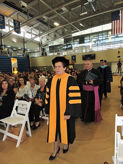 Dr. Rosalie Mirenda, the fifth president of Neumann University, enters the center named after she and her husband, during inauguration of Neumann's sixth president, Dr. Chris Domes.