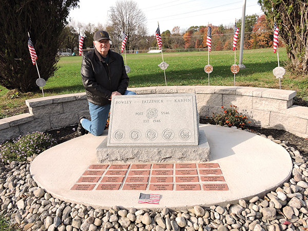 Trainer Councilman James Cassidy poses with the veteran's memorial recently erected in the borough.