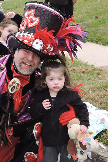 Two year-old Karlie Peterson was paid a special visit by the leader of the Greater Overbrook String Band during the Brookhaven Holiday Parade.