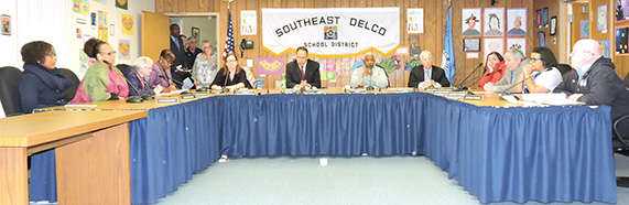 Members of the Southeast Delco School Board prior to the 6-3 vote rescinding the previously approved contract extension of Superintendent of School's Dr. Stephen Butz. From left, Tanya Cavalieri, Tammi Forbes,  Dorothy Gallagher, board secretary Vanessa Scott, Dr. Butz, President Theresa Harris-Johnson, solicitor Robert DiOrio, Racquel Irons, Edward McBride, Sheree Monroe, and Donald Young.