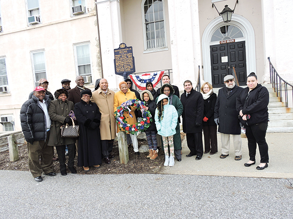 Following a wreath laying ceremony, a group of Chester residents join Rev. Dr. Bayard Taylor, Jr., Chester Councilwoman Elizabeth Williams and Michael Curran, president of Crozer-Chester Medical Center, at the site of the former Crozer Theological Seminary.