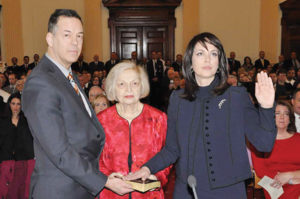 """Katayoun """"Kat"""" M. Copeland (right) was sworn-in with a Bible held by her brother, Cyrus, and her mother, Shahin."""