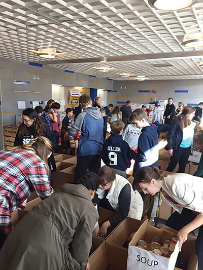 It's organized chaos in the foyer of the Cougar Gym at Springfield High School as students from all levels pack 110 food boxes for community members.