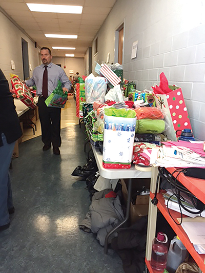"Springfield Superintendent Tony Barber lends a hand to sorting hundreds of gift bags assembled as district personnel become ""angels"" for district children."