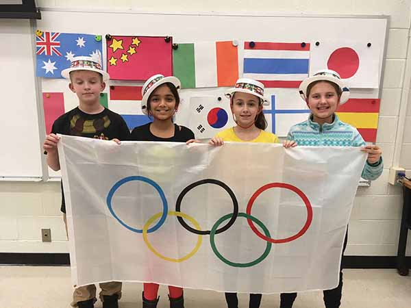 Glenwood Elementary School Olympic Committee members (from left) Ethan Strain, Rayna Patel, Julia Casey and Alexis Maggio, wearing straw skimmers with bands of flags, displayed the Olympic flag.