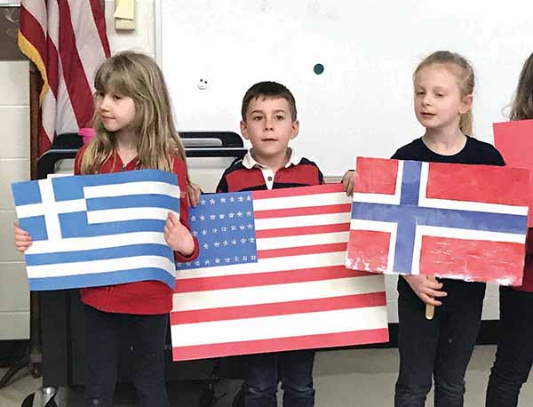 Flag bearers in the Parade of Nations included (from left) second grader Grace Wolff (Greece), kindergartener Caleb Russell (USA) and first grader Nora Cawley (Norway).
